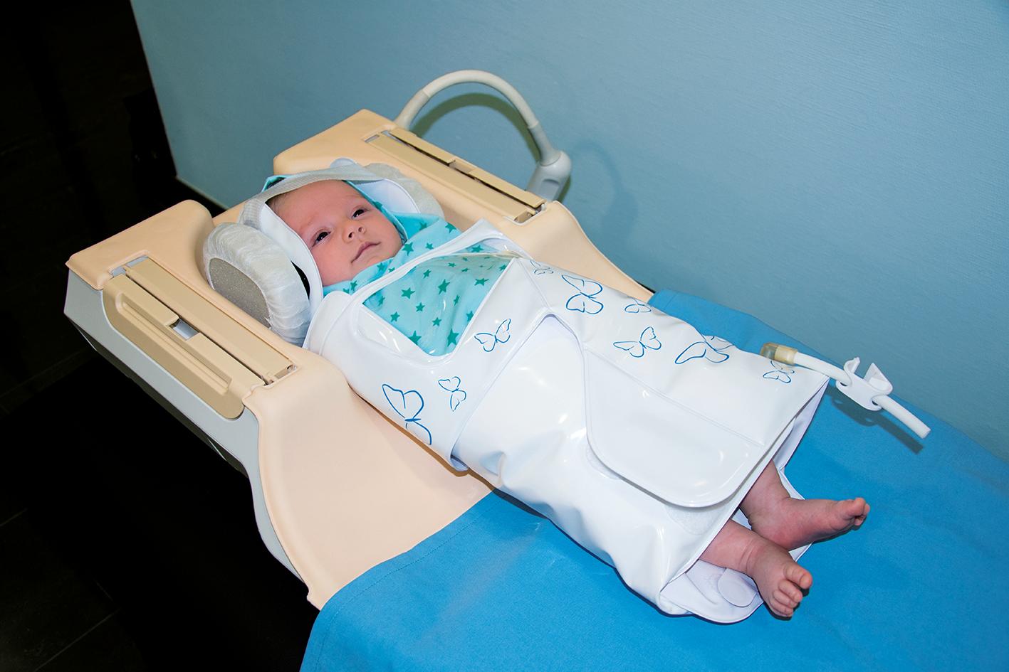 Neugeborenes in Kopfspule in BabyFix Cocoon gewickelt